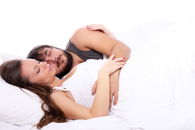 Joven pareja duerme en la cama