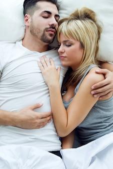 Joven pareja durmiendo en la cama.