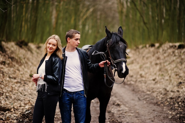 Joven pareja elegante en el amor cerca de caballo en el bosque de otoño