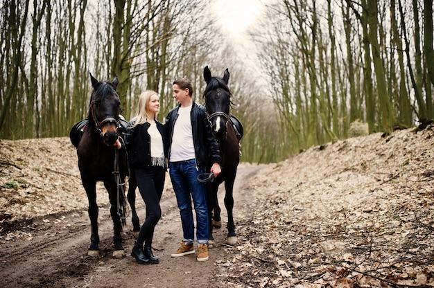 Joven pareja elegante en el amor cerca de caballos en el bosque de otoño