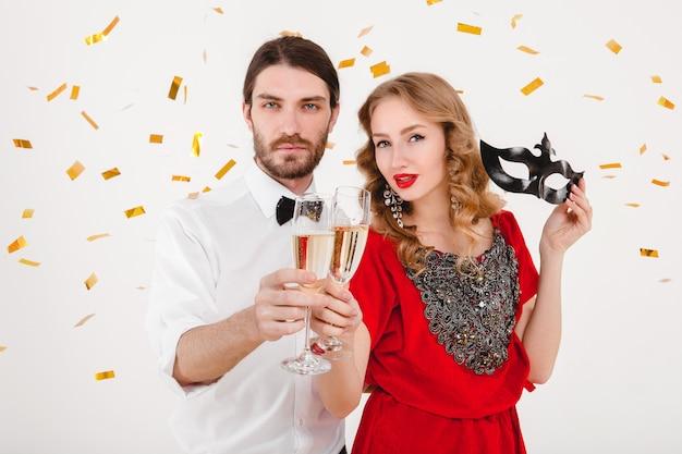 Joven pareja elegante enamorada celebrando el año nuevo y bebiendo champán