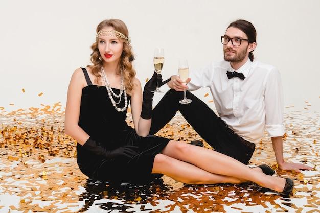 Joven pareja elegante enamorada, sentada en el suelo, lanzando confeti dorado