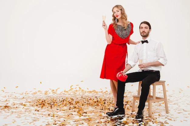 Joven pareja elegante enamorada sosteniendo vasos y bebiendo champán, celebrando el año nuevo