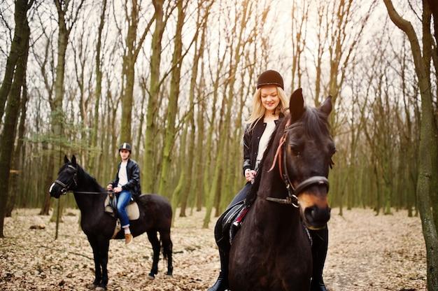 Joven pareja elegante montando a caballo en el bosque de otoño
