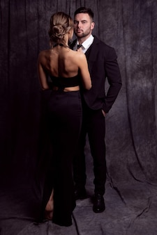 Joven pareja elegante en ropa negra posando