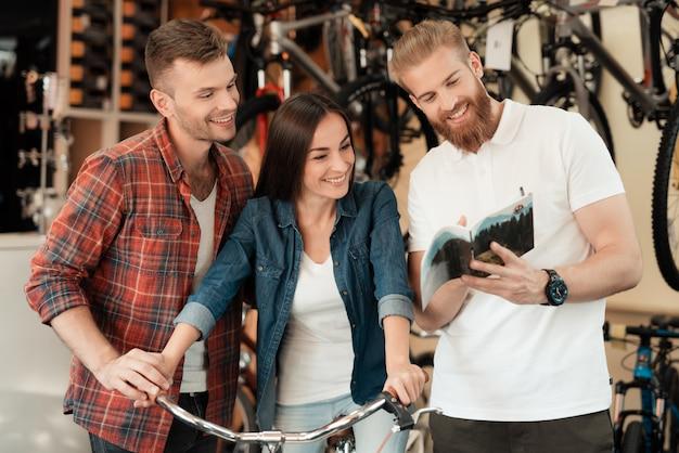 Joven pareja elige nueva bicicleta con consultor