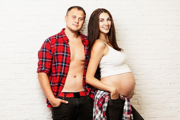 Joven pareja embarazada abrazando y sonriendo. esperando nacimiento y tierna relación.