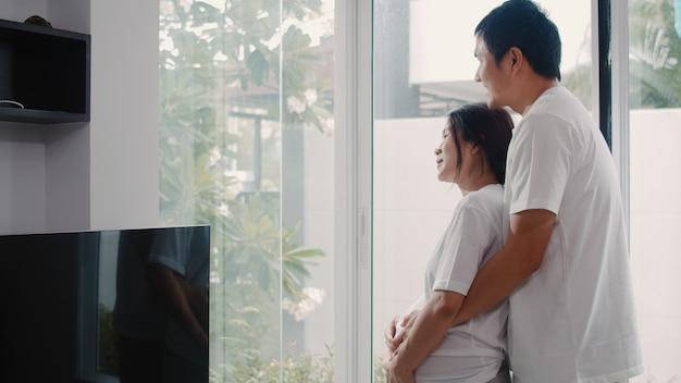 Joven pareja embarazada de asia abraza y sosteniendo el vientre hablando con su hijo. mamá y papá se sienten felices sonriendo pacíficos mientras cuidan bebé, embarazo cerca de la ventana en la sala de estar en casa.