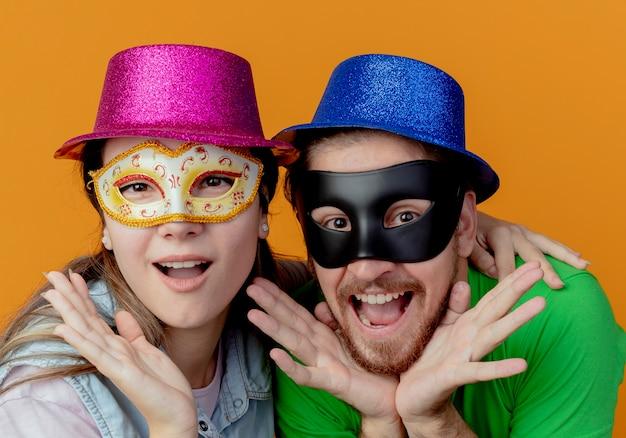 Joven pareja emocionada con sombreros rosados y azules se puso máscaras de ojos de mascarada poniendo las manos en el mentón aislado en la pared naranja