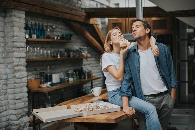 Joven pareja enamorada comiendo pizza en la casa rústica