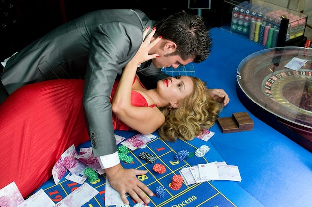 Joven pareja enamorada ganando dinero en las mesas del casino