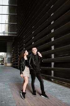 Una joven pareja enamorada, un hombre y una mujer caminan por la ciudad vespertina, pasando tiempo juntos.