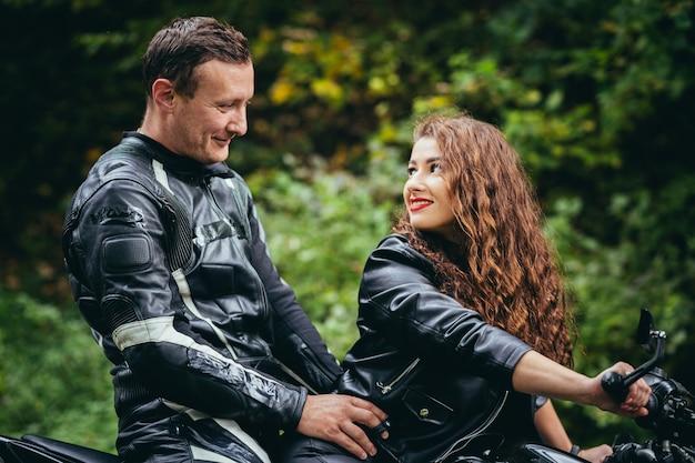 Joven pareja enamorada en una motocicleta en la carretera en el bosque