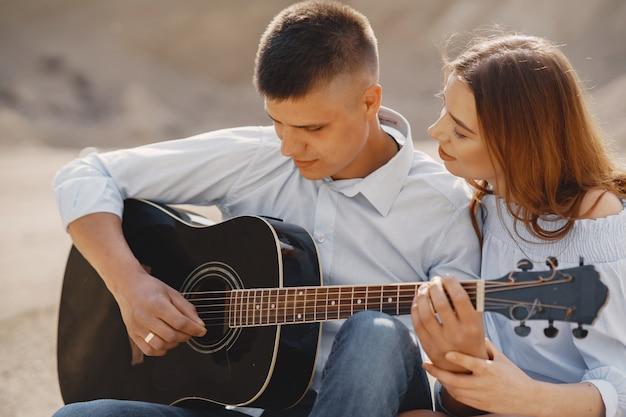 Joven pareja enamorada, novio tocando la guitarra
