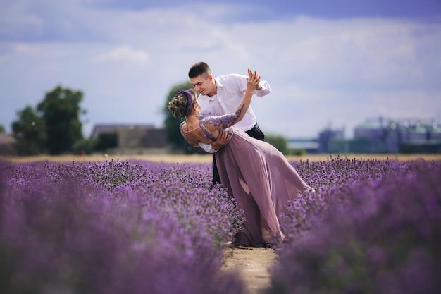 Joven pareja de enamorados abrazándose y bailando en un campo de lavanda en verano
