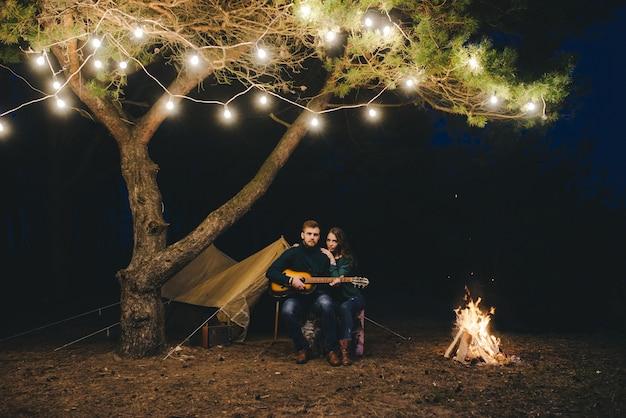 Joven pareja de enamorados acampando turistas sentados junto a un fuego contra una carpa en el bosque con una guirnalda retro, foto con mucho ruido, enfoque selectivo