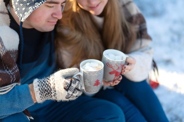 Joven pareja de enamorados bebe una bebida caliente con malvaviscos, sentada en el invierno en el bosque, acurrucada en alfombras cálidas y cómodas y disfruta de la naturaleza
