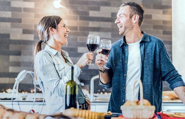 Joven pareja de enamorados bebiendo vino tinto en la cocina de la casa