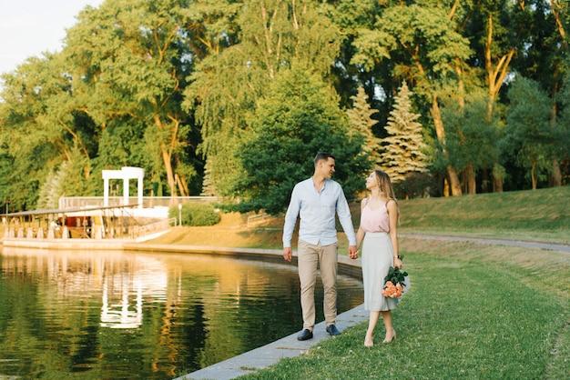 Una joven pareja de enamorados camina a lo largo de la orilla de un lago en un parque de la ciudad. primera fecha