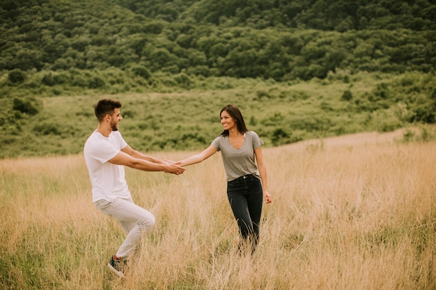 Joven pareja de enamorados caminando por el campo de hierba