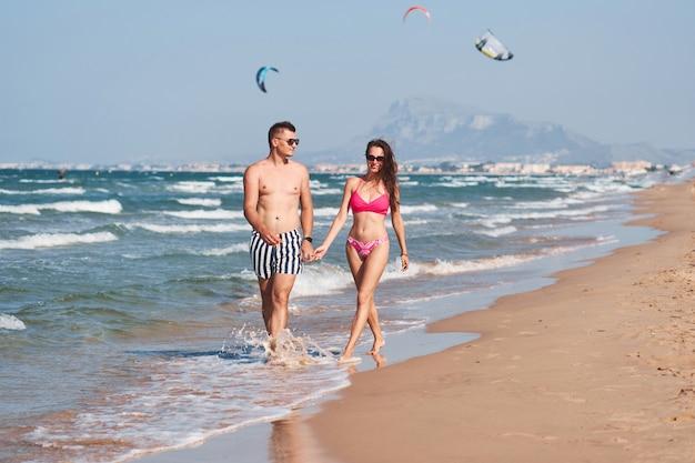 Joven pareja de enamorados caminando por la playa.