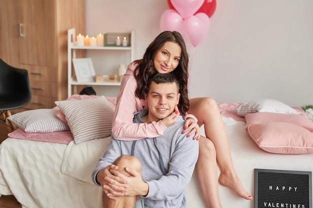 Joven pareja de enamorados en casa en la cama celebrando el día de san valentín