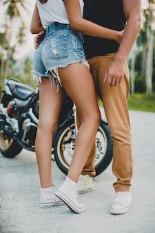 Joven pareja de enamorados cerca de una motocicleta