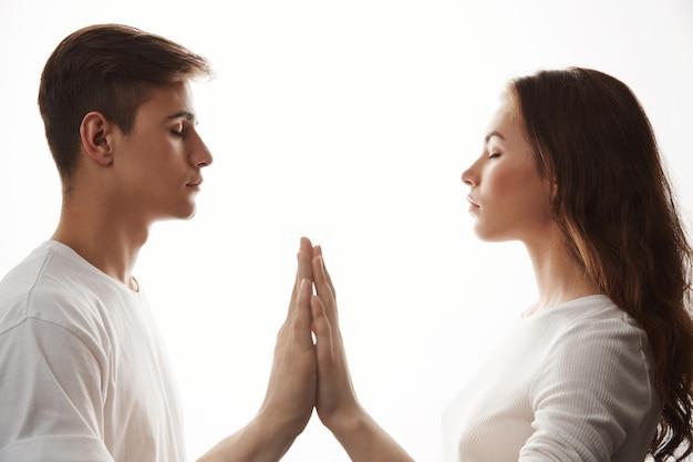Joven pareja de enamorados cogidos de la mano con los ojos cerrados.