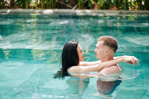 Joven pareja de enamorados de pie en la piscina, abrazándose y mirando el uno al otro