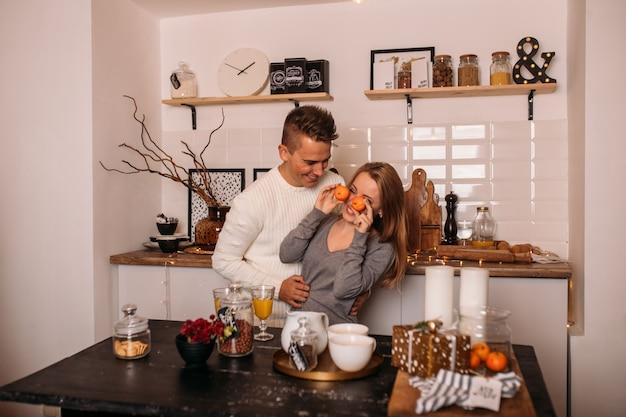 Joven pareja de enamorados riendo y celebrando la navidad en la cocina