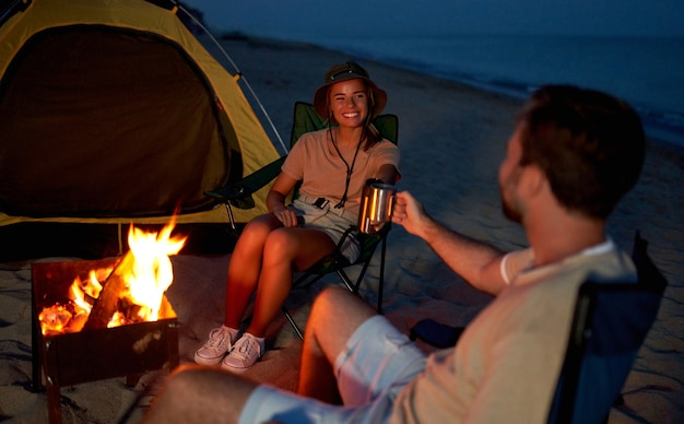 Una joven pareja de enamorados está sentada cerca de la carpa en sillas plegables junto al fuego, bebiendo té por la noche a la orilla del mar.