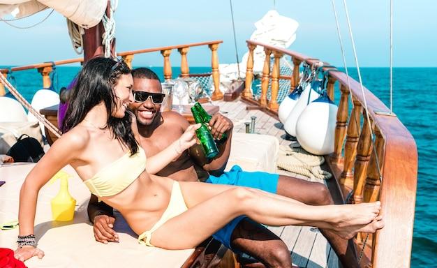 Joven pareja de enamorados en velero animando con botellas de cerveza - feliz novia y novio haciendo fiesta en viajes de crucero en velero de lujo - filtro vívido brillante con enfoque en caras