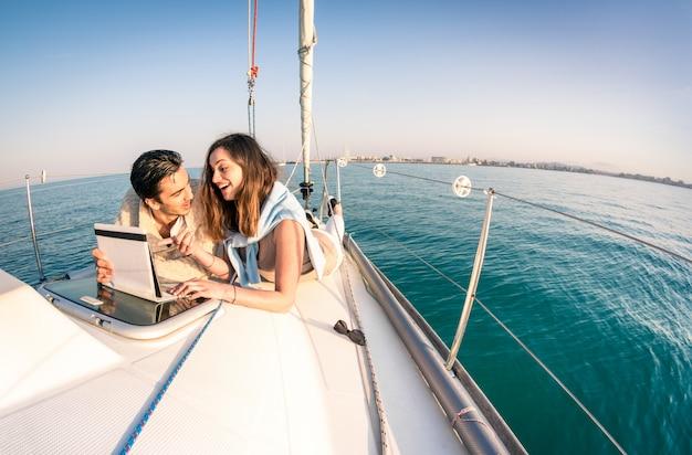 Joven pareja de enamorados en velero divirtiéndose con tableta