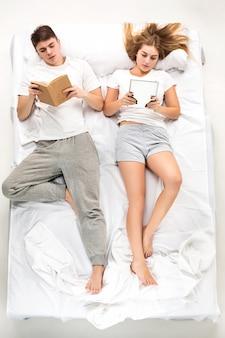La joven pareja encantadora acostada en una cama con libros