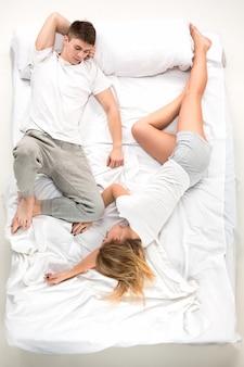 La joven pareja encantadora acostada en una cama