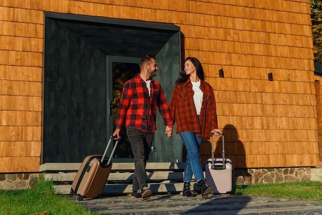 Joven pareja encantadora caucásica con equipaje saliendo de casa para vacaciones. concepto de familia feliz.