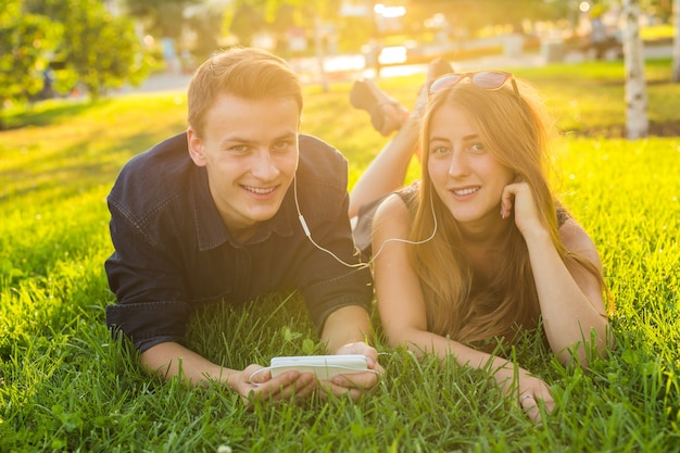 Joven pareja encantadora caucásica o estudiantes universitarios acostados juntos en el césped, escuchando música. concepto de amor, relación, verano y estilo de vida.