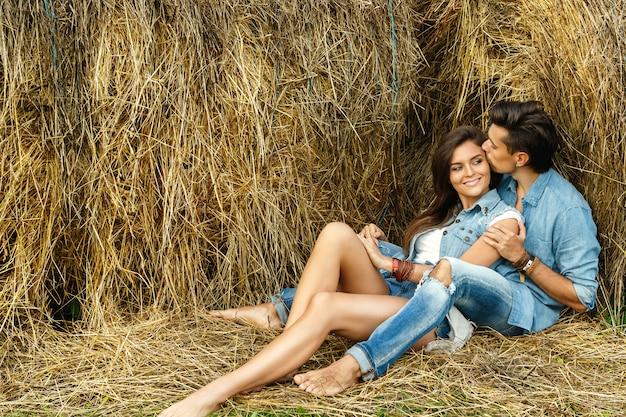 Joven pareja encantadora se relaja entre los pajar