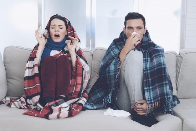 Joven pareja enferma está sentado en el sofá con alfombras.