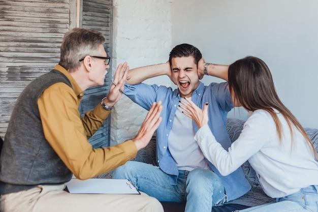 Joven pareja enojada después de la sesión de terapia con psicólogo familiar