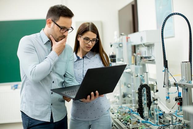 Joven pareja de estudiantes con computadora portátil en el laboratorio de robótica