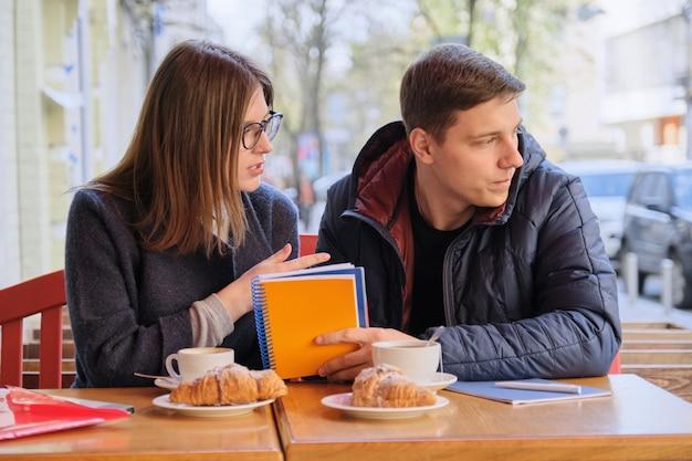 Joven pareja de estudiantes estudian en un café al aire libre