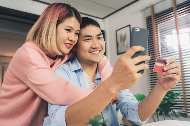 Joven pareja de familia asiática usando teléfono inteligente discutiendo noticias