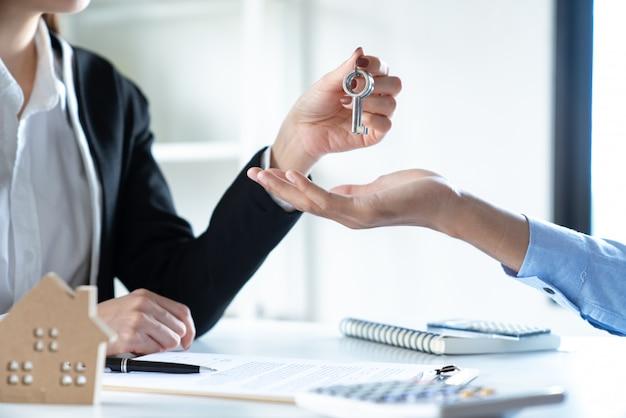 Joven pareja familiar obteniendo la llave de la casa del agente inmobiliario después de firmar un contrato de contrato de préstamo hipotecario