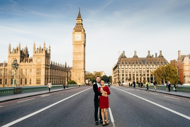Joven pareja familiar de pie en el puente de westminster en el fondo con el big ben, disfruten del tiempo libre juntos en londres