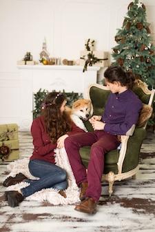 Joven pareja feliz abrazando al adorable perro akita inu mientras se sienta en un elegante sillón retro para las vacaciones de navidad en casa, el árbol de navidad y la chimenea, acogedoras decoraciones para el hogar