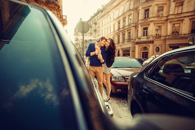 Joven pareja feliz abrazando en la calle de la ciudad.