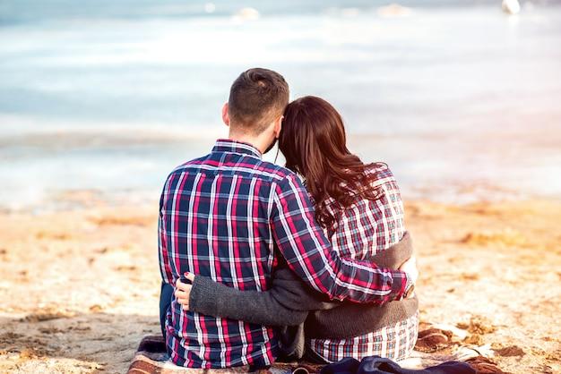 Joven pareja feliz al aire libre en la playa