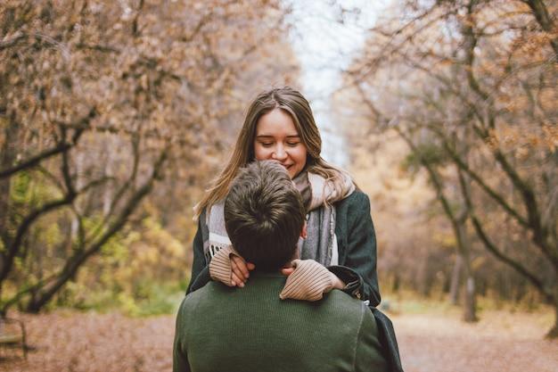 Joven pareja feliz en amor amigos vestidos con estilo casual caminando juntos en el parque otoño