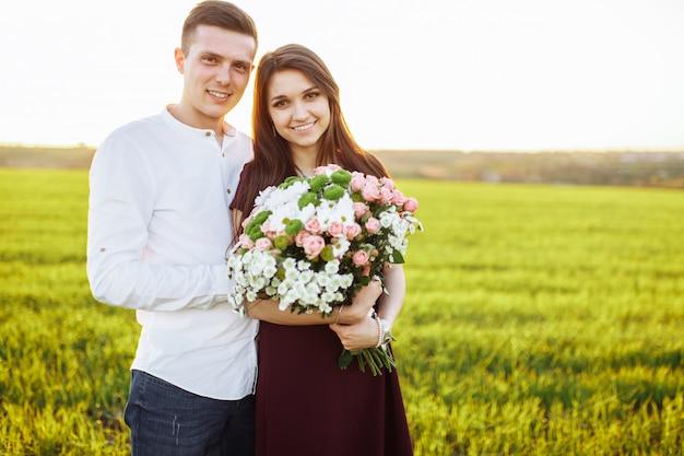 Joven pareja feliz en el amor, mujer sosteniendo flores, felices y disfrutar de la compañía del otro